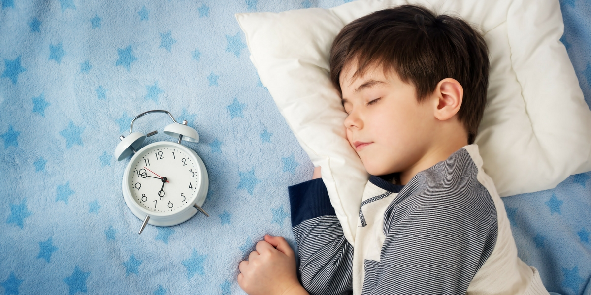 little boy in bed with clock