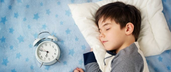 little boy in bed with a clock beside him