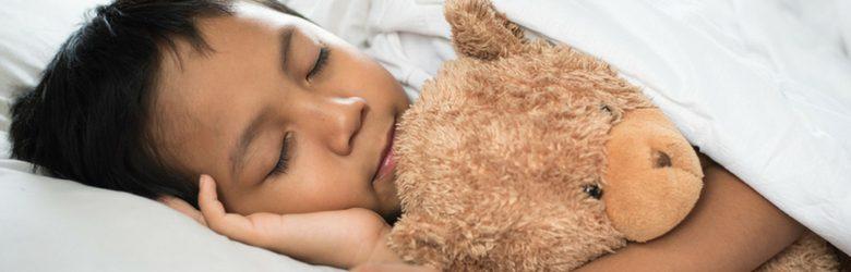 little boy in bed with teddy bear