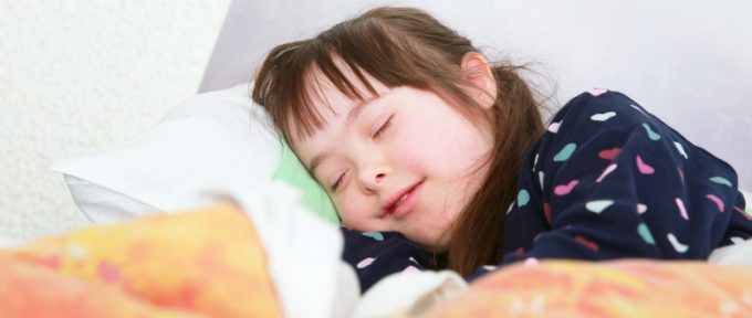 young down syndrome girl in bed